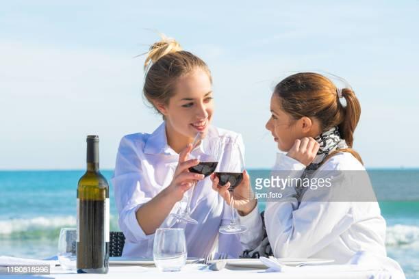 best friends celebrating beach drink red