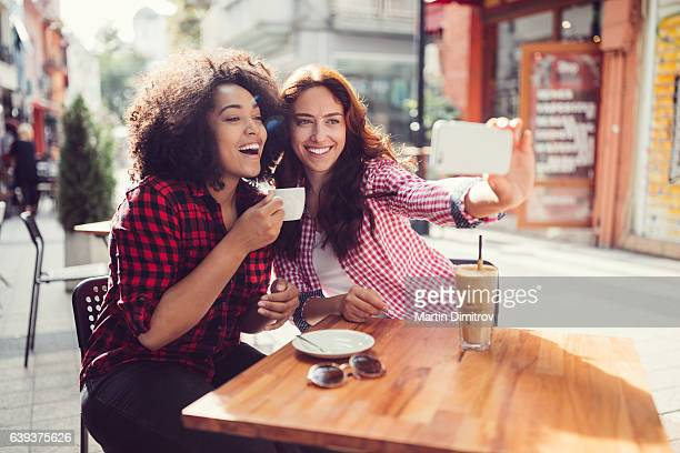 best friends drinking coffee and taking photos - pavement cafe stock pictures, royalty-free photos & images