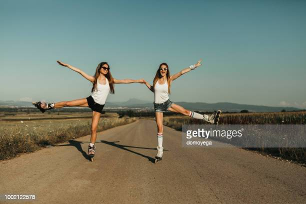 best friends having fun on a sunny day and driving inline skates - inline skating stock pictures, royalty-free photos & images