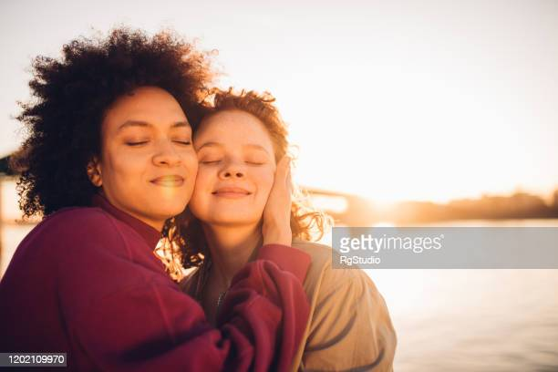 best friends hugging and enjoying the sunset - international womens day stock pictures, royalty-free photos & images