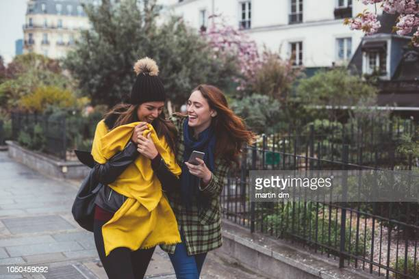 best friends in paris walking while texting - ile de france stock pictures, royalty-free photos & images
