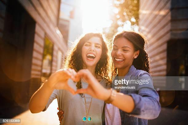 Besten Freunde lachen während zeigen Herz mit Händen