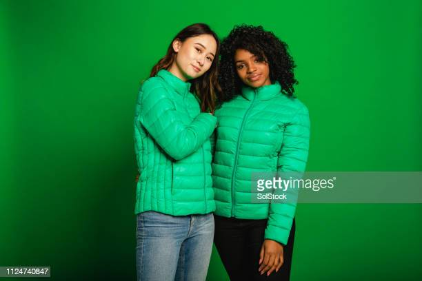 best friends - green coat stock pictures, royalty-free photos & images
