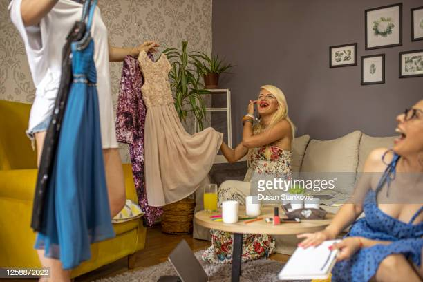 best friends planning the night out by choosing the outfits and dressing up together - sleeveless stock pictures, royalty-free photos & images