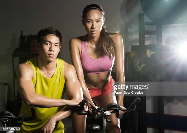Best friends posing on a stationary bike after their spinning class
