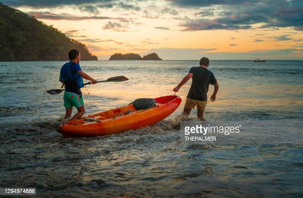 best friends putting a kayak into the waves costa rica - guanacaste stock pictures, royalty-free photos & images
