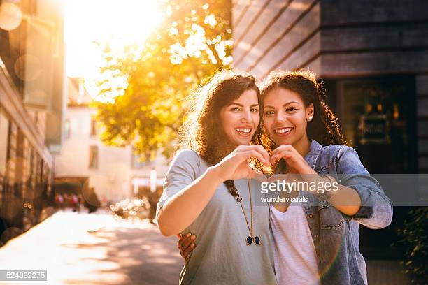 Best Friends Show Heart Towards Camera With Hands