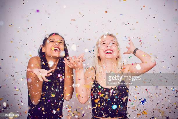 Best friends smiling under confetti rain