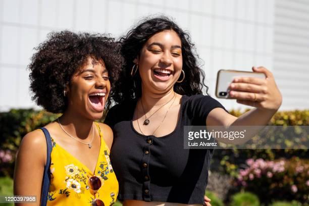 best friends taking selfie outdoors - afro americano foto e immagini stock