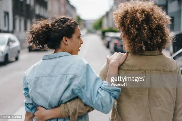 best friends walking in the city, arm in arm, rear view - amigos abrazados espaldas fotografías e imágenes de stock