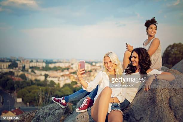 Best girlfriends are looking the city from above and taking selfie/making video call