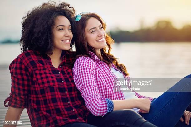 beste vriendinnen zoekt de zonsondergang over het meer - lesbische stockfoto's en -beelden
