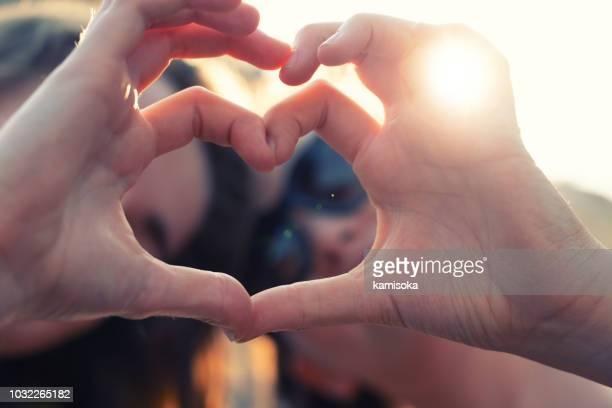 beste freundinnen machen herzförmige händen - herz stock-fotos und bilder