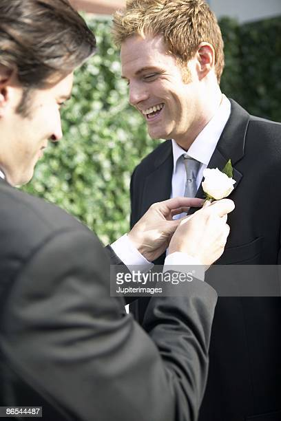 Best man adjusting groom's boutonniere