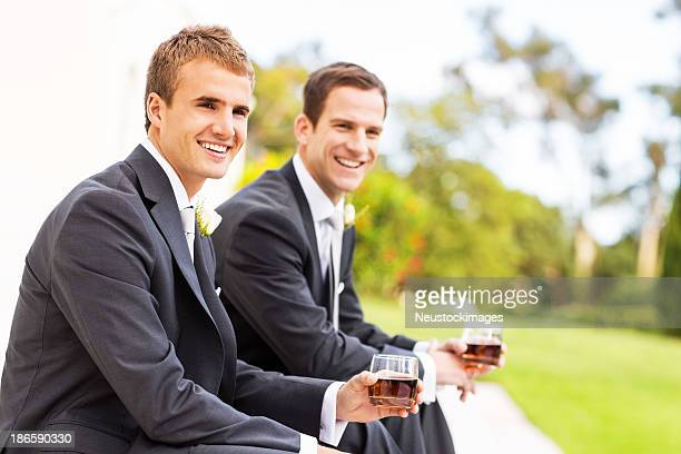 Best Man And Groom With Whisky Glasses Sitting In Garden