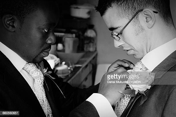 best man fixing tie of groom - marriage stock pictures, royalty-free photos & images