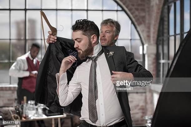 Best man helping groom getting ready before the wedding