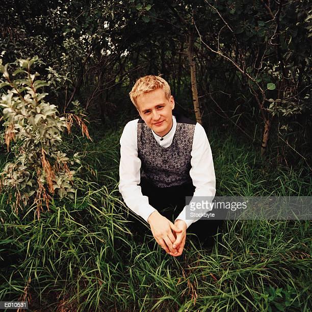 Best man kneeling in greenery