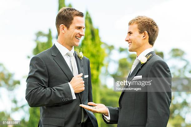Best Man Looking At Groom While Showing Wedding Rings
