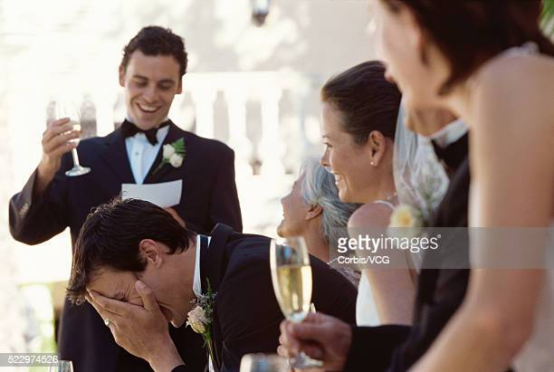Best man making a speech on the head table at a wedding reception