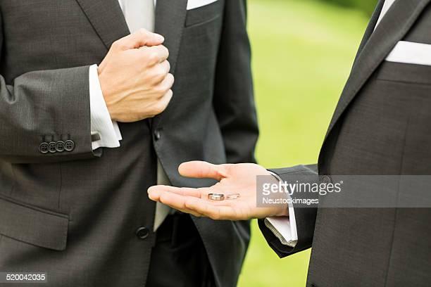 Best Man Showing Wedding Rings To Groom