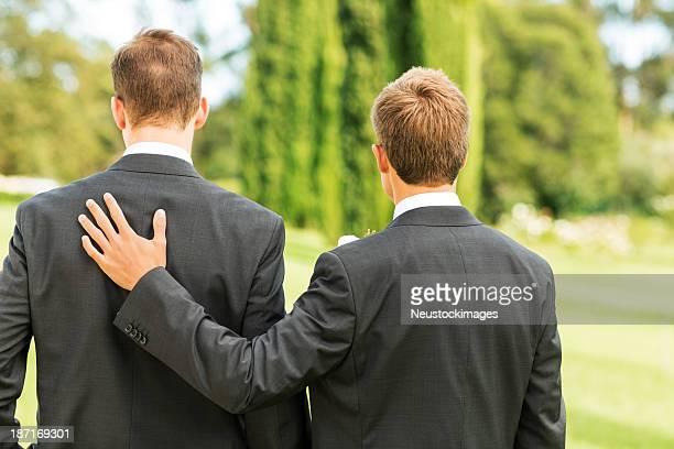 Meilleur homme debout avec la main sur le futur marié dans le jardin