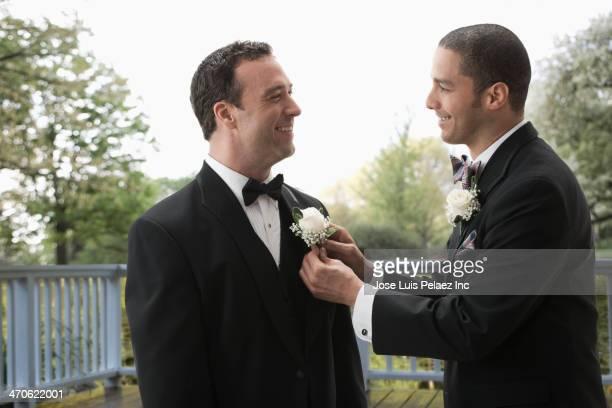 Best man tying groom's boutonniere