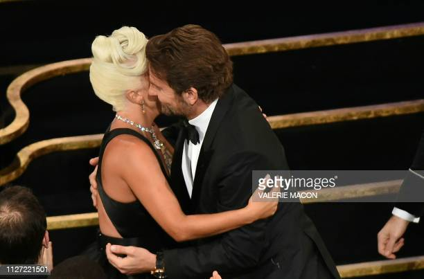 TOPSHOT Best Original Song nominees for Shallow from A Star is Born Lady Gaga embraces actor Bradley Cooper as she accepts the award for Best...
