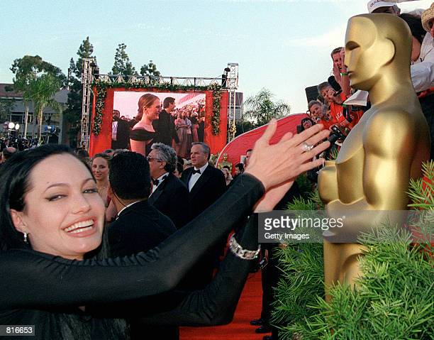 Best Supporting Actress Nominee Angelina Jolie reaches over to touch the Oscar statue at the 72nd Annual Academy Awards March 26 2000 in Los Angeles