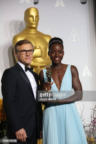 Best supporting actress winner Lupita Nyong'o and Christoph Waltz pose in the press room of the 86th Academy Awards aka Oscars at Dolby Theatre in...