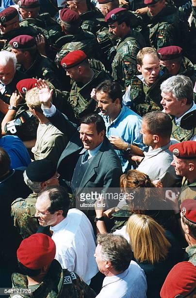 Besuch von Bundeskanzler Gerhard Schröder in Prizren / Kosovo: Schröder in der Menschenmenge, umgeben von Bodyguards und Bundeswehrsoldaten; hinter...