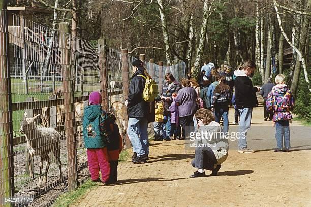 Besucher an einem sonnigen Frühlingstag am Hirsch-Gehege im Wildpark Lüneburger Heide. Im Vordergrund sitzt eine Frau in der Hocke, um ihre Kinder am...