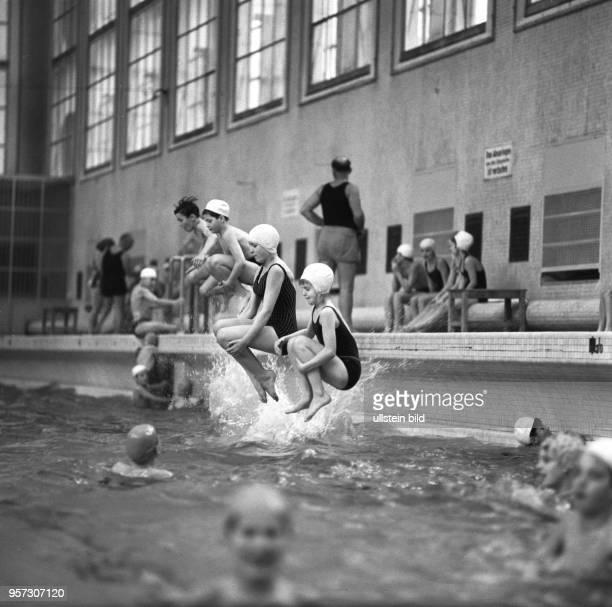 Besucher einer Schwimmhalle springen vom Beckenrand ins Wasser, aufgenommen 1976 in Berlin-Baumschulenweg.