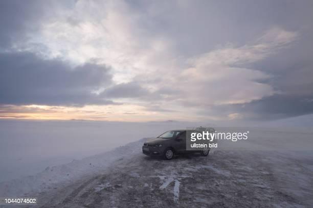 Besucher stehen mit Fahrzeugen in einem Eissturm mittin in schneebedeckte Landschaft des Thingvellir Nationalparks an der Route 36