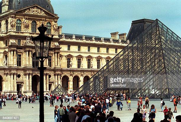 Besucherströme stehen Schlange vor der Glaspyramide vor dem Louvre die den Eingang zu dem Museum bildet