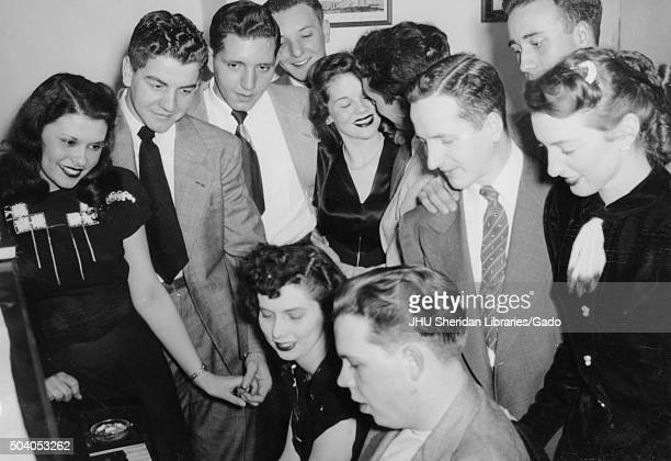 Beta Theta Pi Fraternities Student Life Candid shot of fraternity members and their girlfriends gathering around a piano 1947