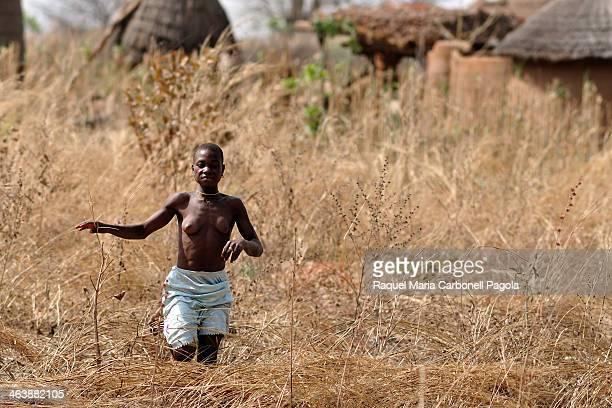 Betamaribe woman running through 'tata sombas' traditional houses