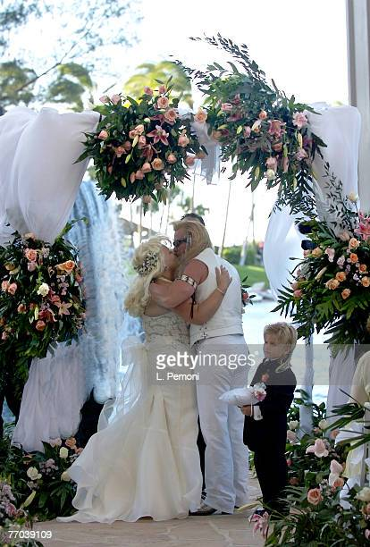 """Beth Chapman wife of Bounty Hunter Duane """"Dog"""" Chapman kiss under an archway of roses near the waterfall at the Hilton Waikoloa Village in Waikoloa,..."""