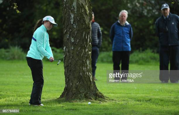 Beth Coulter plays a left handed shot from behind a tree on the 18th hole during the final round of the Girls' U16 Open Championship at Fulford Golf...