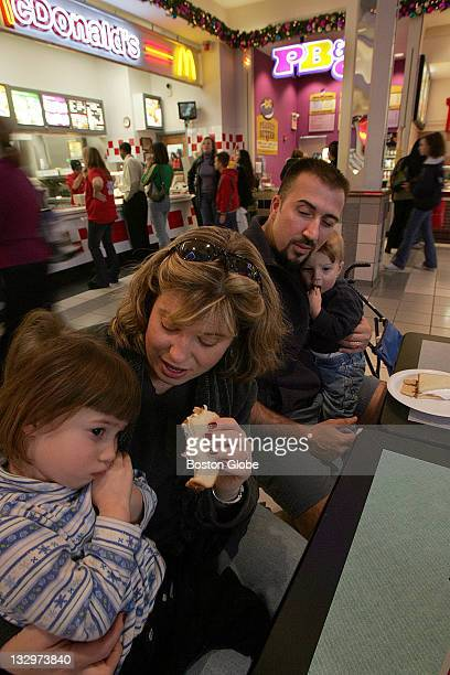 Beth Francis tries to tempt a tired daughter Natalia with a peanut butter and fluff sandwich at the food court at the Northshore Mall Looking on are...