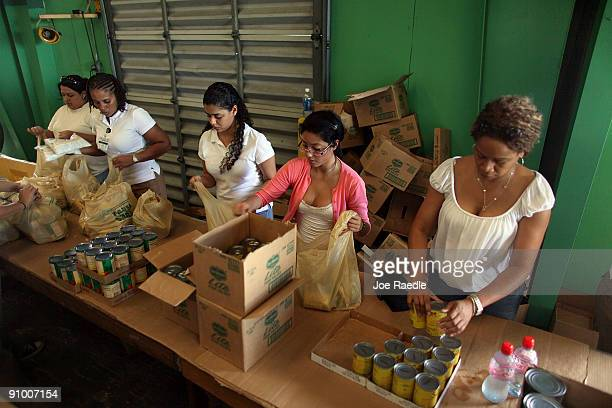 Beth Frazier Carol Echeverria Angie Solomon and Andrea Bloomfield along with other volunteers sort food into individual bags to be given out at Farm...