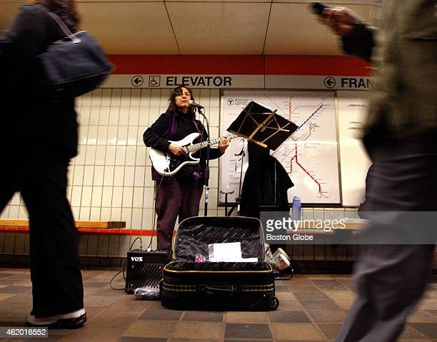 Beth Fridinger of the West Roxbury neighborhood plays to passersby inside the MBTA Downtown Crossing Orange Line station