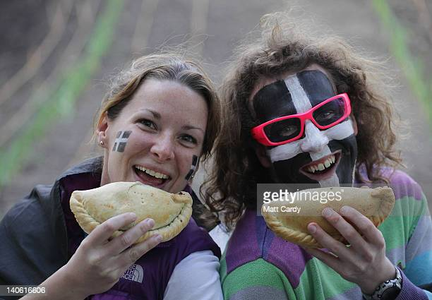 Beth Mitchell 27 and Rory Campbell both from St Austell and sporting Cornish flags painted on their faces try a Cornish pasty that has been baked as...