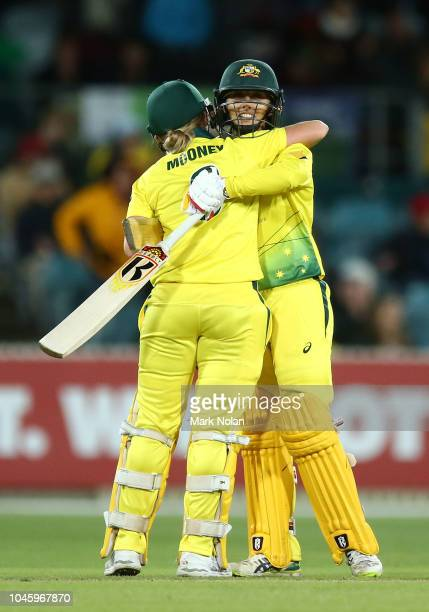 Beth Mooney and Ashleigh Gardner of Australia celebrate winning game three of the Twenty20 series between Australia and New Zealand at Manuka Oval on...