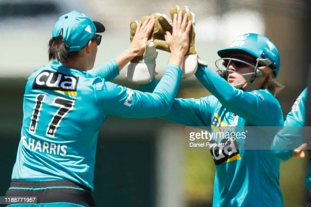 Beth Mooney of the Heat celebrates with Grace Harris of the Heat after dismissing Josie Dooley of the Renegades during the Women's Big Bash League...