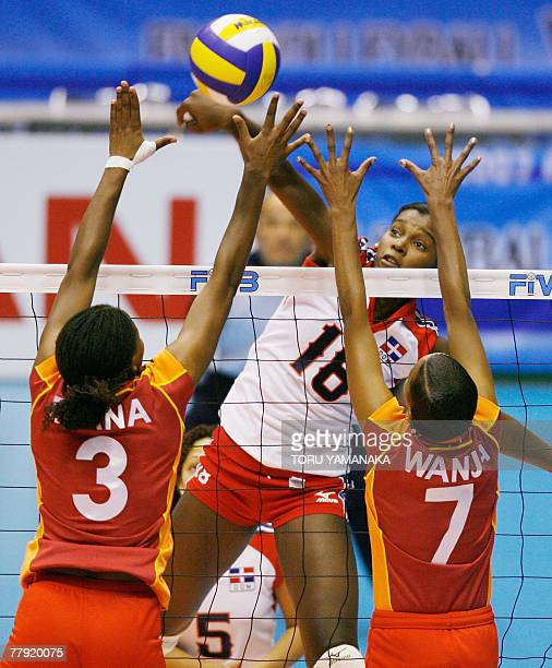 Bethania De La Cruz de Pena of the Dominican Republic spikes the ball over the block of Kenya's Diana Khisa and Janet Wanja during their fourth round...