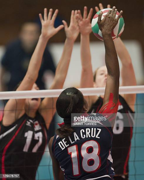 Bethania de la Cruz of Dominican Republic shoots in front of Brittney Page and Jennifer Hinze of Canada during their preliminary volleyball match at...