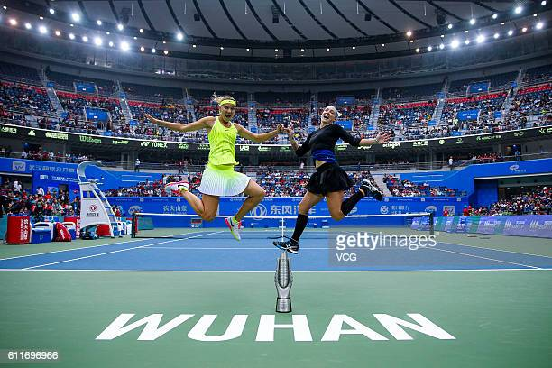 Bethanie Mattek-Sands of the United States and Lucie Safarova of the Czech Republic jump for pictures after winning the women's doubles final match...