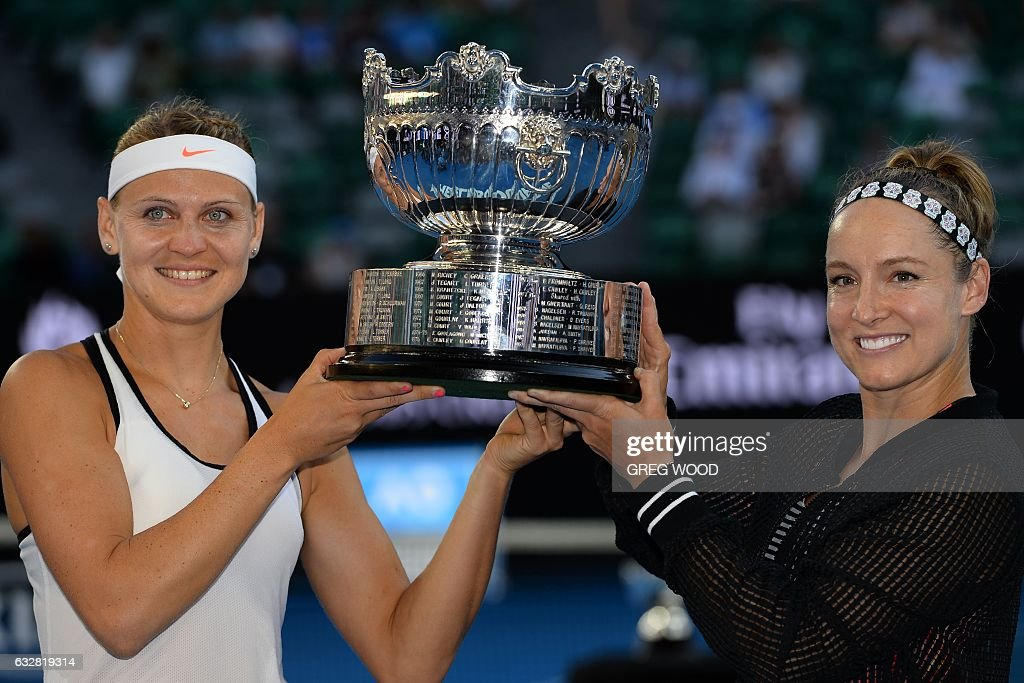 Bethanie Mattek-Sands of the US (R) and the Czech Republic's Lucie Safarova celebrate with the championship trophy after their victory against the Czech Republic's Andrea Hlavackova and China's Peng Shuai in the women's doubles final on day 12 of the Australian Open tennis tournament in Melbourne on January 27, 2017. / AFP / GREG