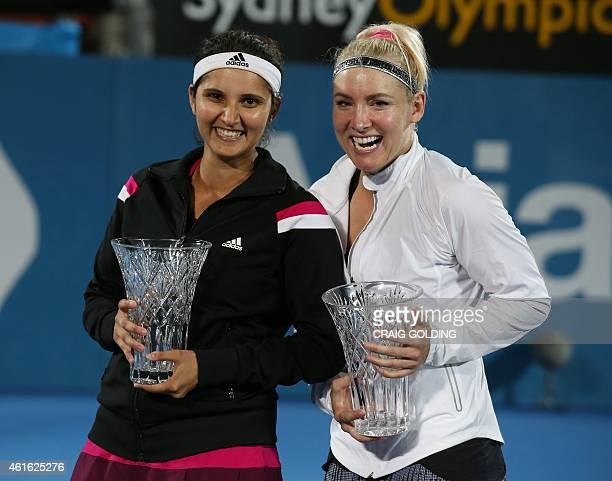 Bethanie Mattek-Sands of the USA and Sania Mirza of India pose with the trophy after winning the women's doubles final against Raquel Kops-Jones of...